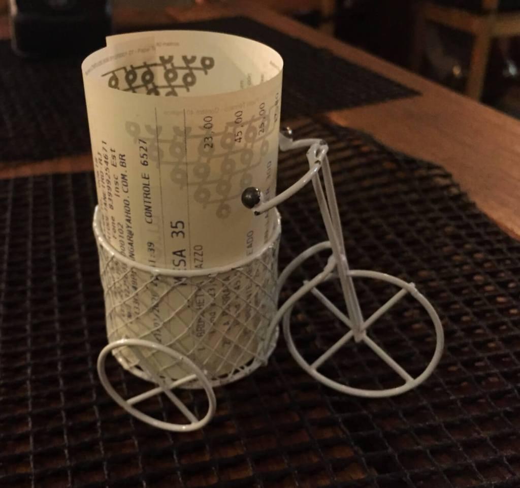 a conta em uma mini bicicleta de mesa na Mazzo Pizzaria com os3fominhas